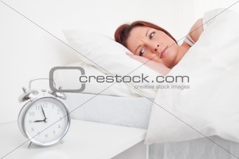 Charming red-haired female waking up thanks to an alarm clock