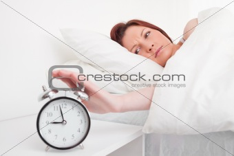 Beautiful red-haired female waking up thanks to an alarm clock