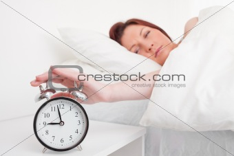 Attractive red-haired female waking up thanks to an alarm clock