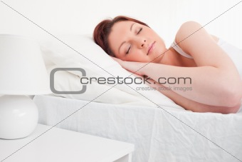 Beautiful red-haired female sleeping in her bed