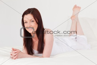 Beautiful red-haired female having a rest while lying on her bed