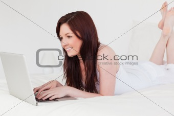 Attractive red-haired female relaxing with her laptop while lyin