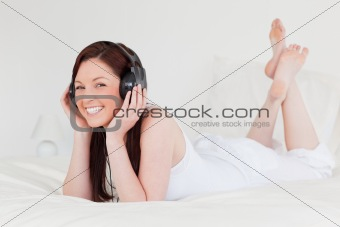 Attractive red-haired female relaxing with her headphones while