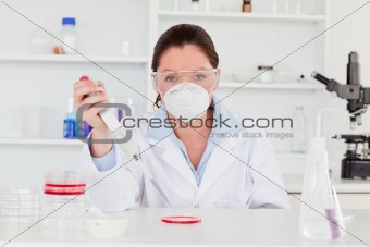 Young scientist preparing a sample wearing a mask