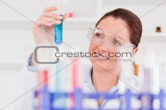 Beautiful scientist lookin at a tube test