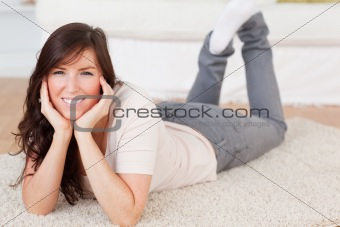 Charming brunette female posing while lying on a carpet