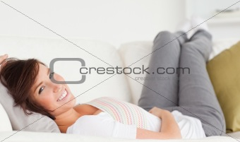 Attractive brunette woman posing while lying on a sofa