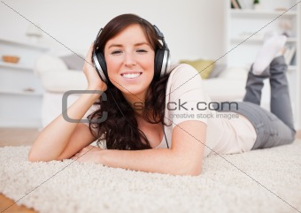 Smiling brunette female using headphones while lying on a carpet
