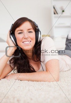Charming brunette woman using headphones while lying on a carpet