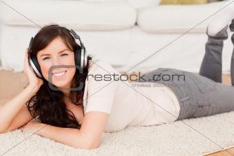 Beautiful brunette woman using headphones while lying on a carpe