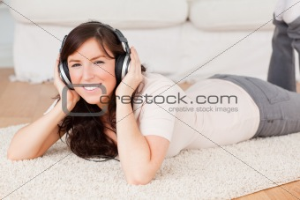 Attractive brunette woman using headphones while lying on a carp