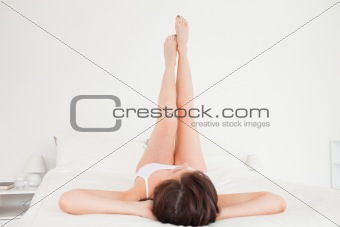 Attractive brunette female stretching her legs while lying