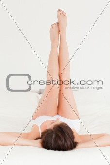 Charming brunette female stretching her legs while lying