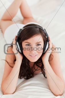 Attractive female with headphones lying