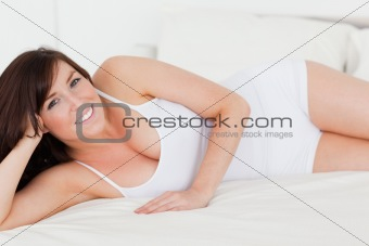 Attractive brunette woman posing while lying