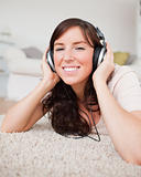 Cute smiling woman using headphones while lying on a carpet