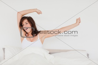 Charming brunette woman posing while stretching