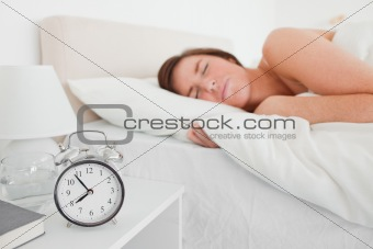 Charming brunette woman awaking with a clock while lying