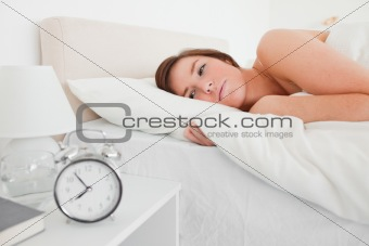 Beautiful brunette woman awaking with a clock while lying