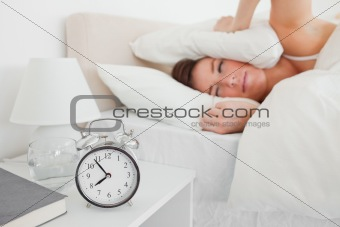 Attractive brunette woman awaking with a clock while lying
