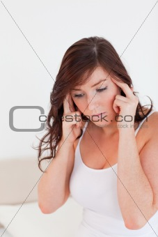 Attractive brunette woman having a headache while sitting