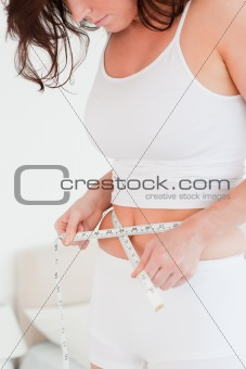 Charming brunette woman measuring her belly with a tape measure