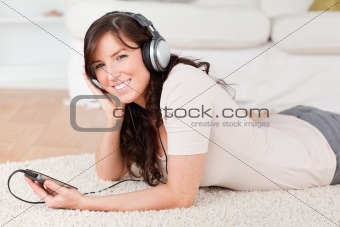 Attractive brunette female listening to music with her mp3 playe