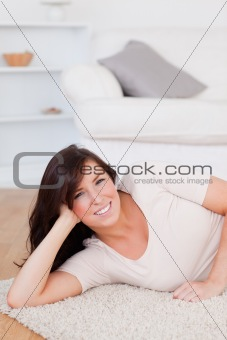Charming brunette woman posing while lying on a carpet