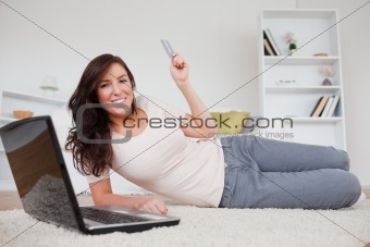 Attractive brunette female making a payment with a credit card o