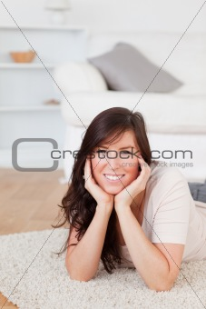 Attractive brunette female posing while lying on a carpet