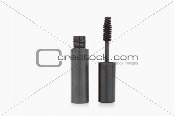 A black mascara brush and tube