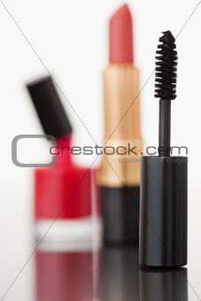 A mascara tube with a lipstick and a nail polish flask