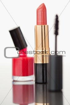 A mascara tube with a pale red lipstick and a nail polish flask