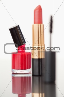 A mascara tube with a pale red lipstick and a red nail polish fl