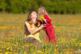 mother and son picking flowers at dandelion field in spring