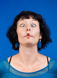 middle-aged woman making funny faces - isolated on blue