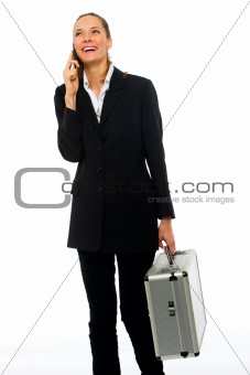 Young businesswoman on a cell phone with a briefcase on white background studio