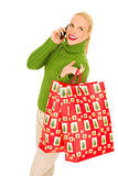 Woman with mobile and bags with Christmas gifts