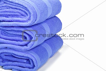 Three blue towels on a white with space for text