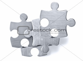 Stainless steel puzzle pieces on white background