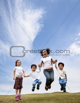 happy asian family  jumping on the grass field.