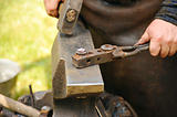 Blacksmith hammering hot steel on anvil