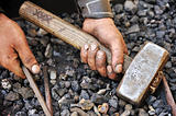 Detail of dirty hands holding hammer and rod - blacksmith