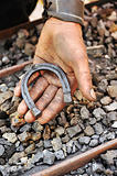 Detail of dirty hand holding horseshoe - blacksmith