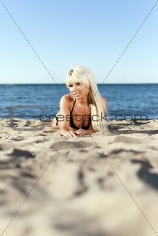 blonde girl in a black bathing suit lying on the shore of the blue sea