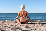 blonde girl in a black bathing suit sits on the beach and meditate