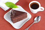 Chocolate cake and a cup of coffee on a brown background