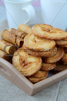 Assorted cookies, puff and waffle in a wooden bowl