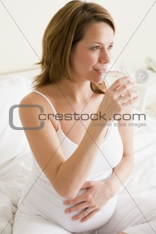 Pregnant woman sitting in bedroom with glass of water smiling