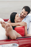 man and beautiful woman hugging in cabriolet car